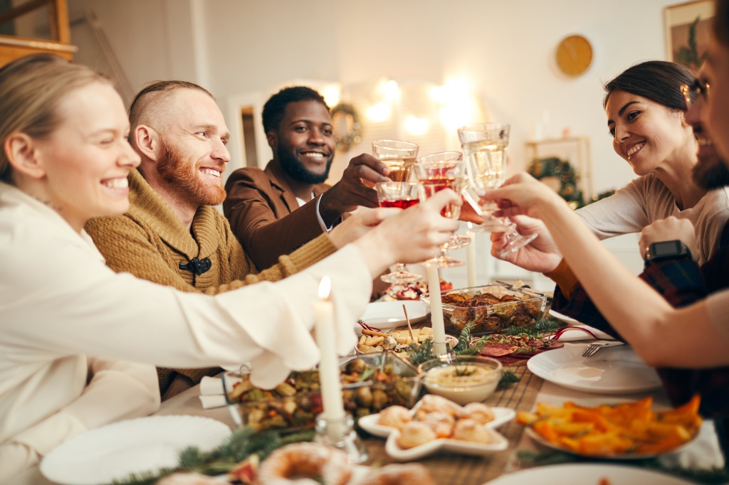 Multi-ethnic group of people raising glasses sitting at beautiful dinner table celebrating Christmas with friends and family